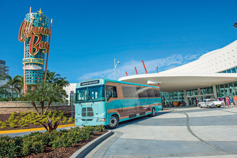 Retro bus leaves the roundabout in front of the Cabana Bay Beach Resort.