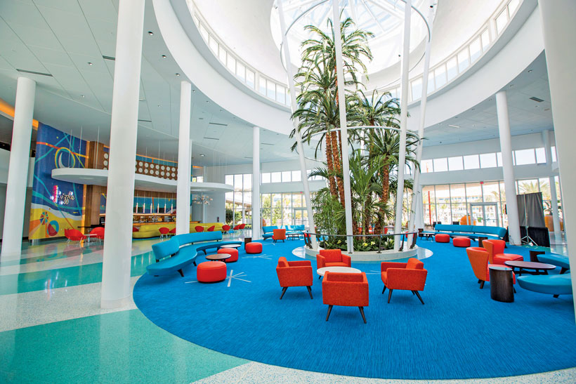 Retro hotel lobby has a round blue carpeted area with bright orange chairs, white pillars and palm trees beneath the middle of a domed glass ceiling.