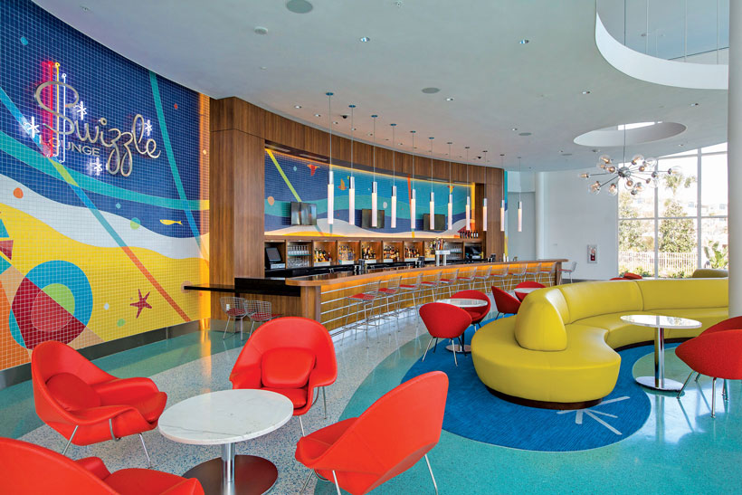 Brightly colored retro hotel bar area has futuristic furniture, funky painted walls and shiny blue floors.