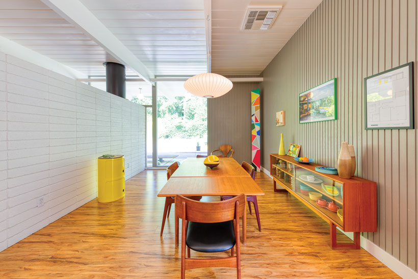 The Eichler dining room has wood flooring, paneled walls and a large pendant light.