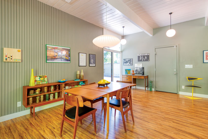 The Eichler home dining room is adjacent to the kitchen and has sage green walls.