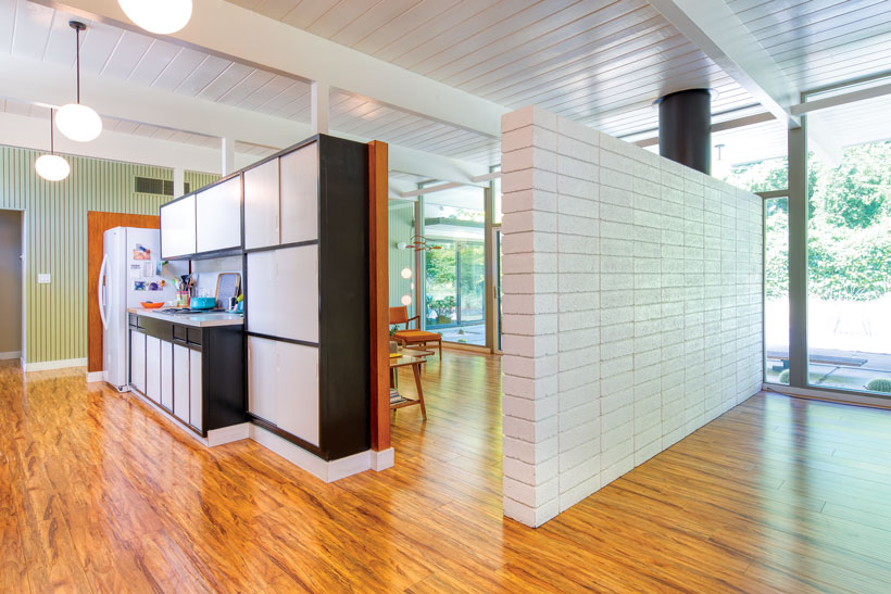 The Eichler home kitchen is closed off from the rest of the house with thick, white-painted walls in mid century style.