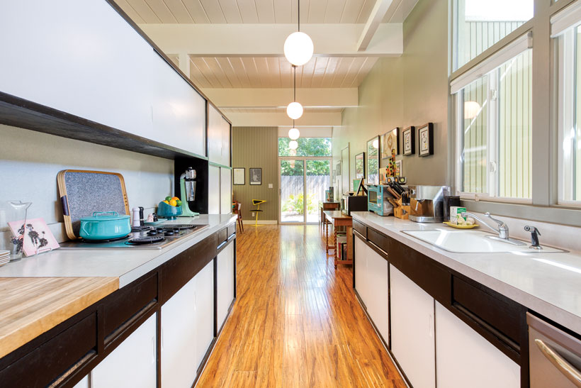 The kitchen has white cabinetry with black trim and wood flooring.