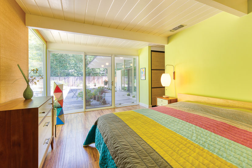 The colorful bedspread complements sage green walls and has sliding glass doors leading out to the backyard patio of the Eichler home.
