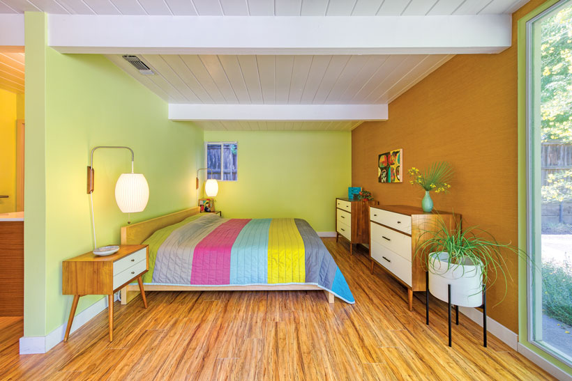 Open bedroome with mid century furniture and sage green walls.