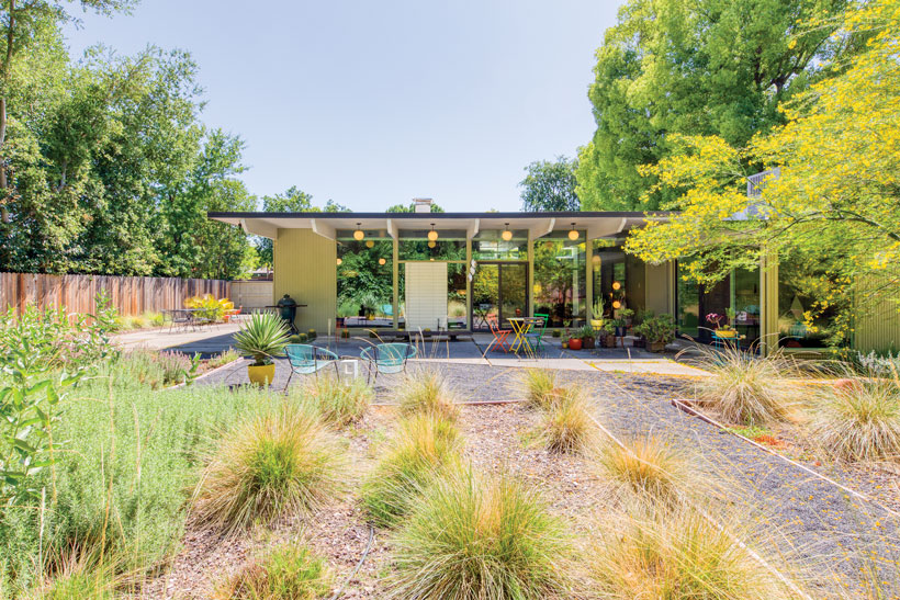 The Eichler home backyard has tufts of grass and gravel pathways that lead to the back patio.