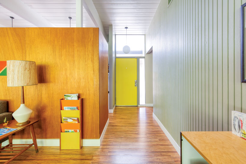 The hallway leads towards the front door's bright yellow interior side.