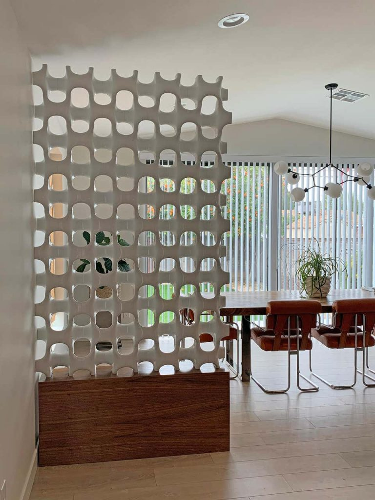 A Richard Harvey sculpta grille screen, white honeycomb room divider on walnut base placed in front of chrome dining room set in front of white vertical blinds.