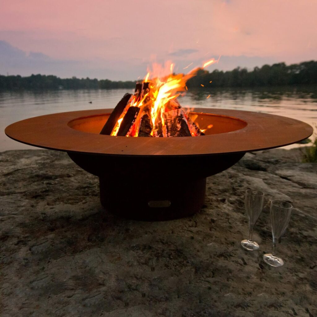 Carbon steel modern fire pit with burning fire near a body of water.