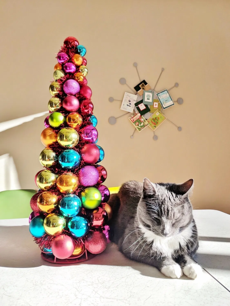 Colorful retro holiday ornament tree with a sleeping cat and a Christmas card holder in the shape of a starburst