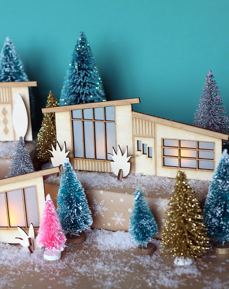 Retro holiday village made of wooden Midcentury home cutouts and assorted bottlebrush trees