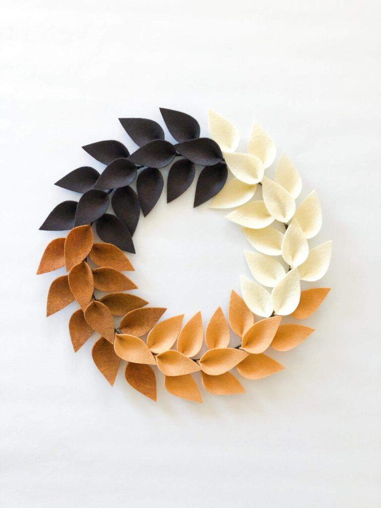 Orange, brown, white and black minimalist wreath with felt leaves.