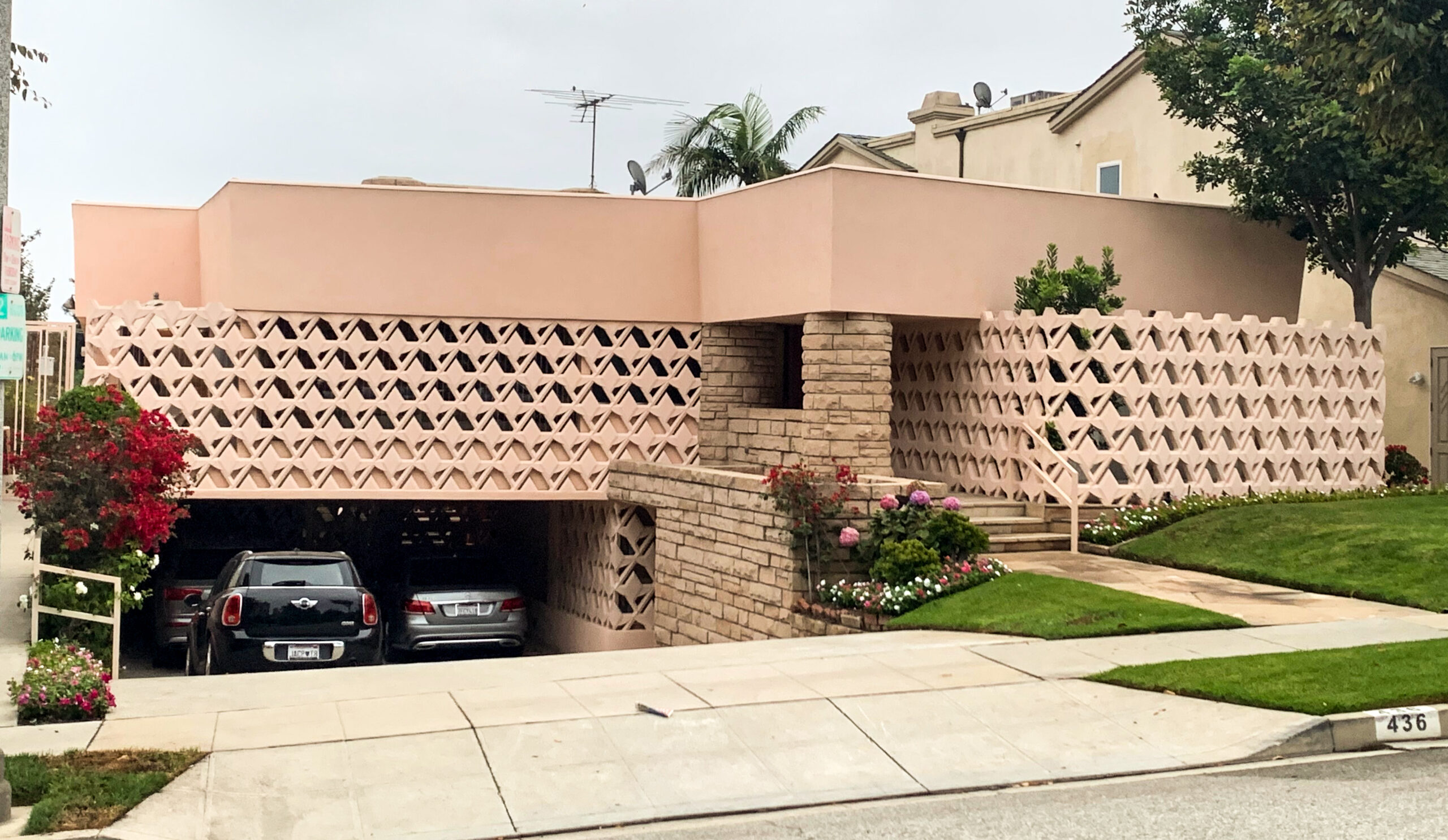A pink home with textured pink blocks that wrap around the facade