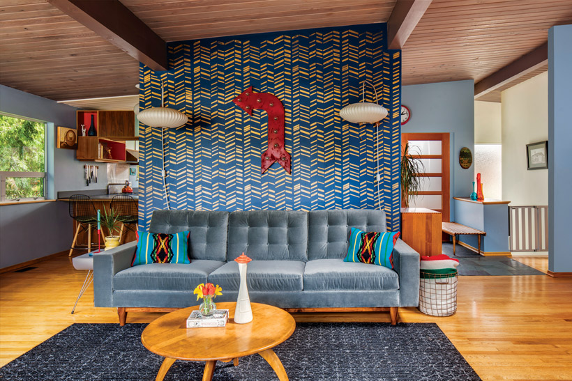 A midcentury-style living room has a blue stenciled wall for a background that makes the lamps pop.