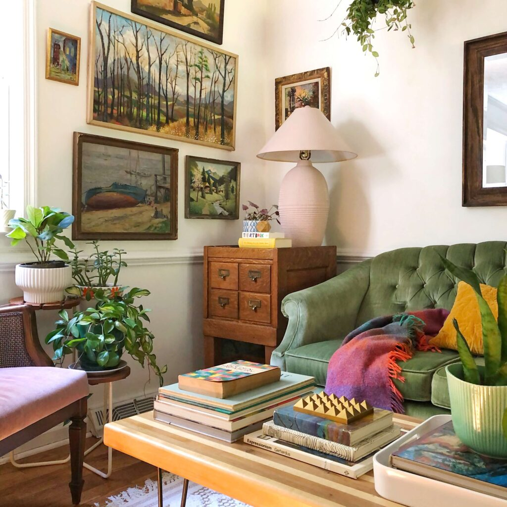 This living room corner has vintage artwork of landscapes, a green couch and a wooden side table.