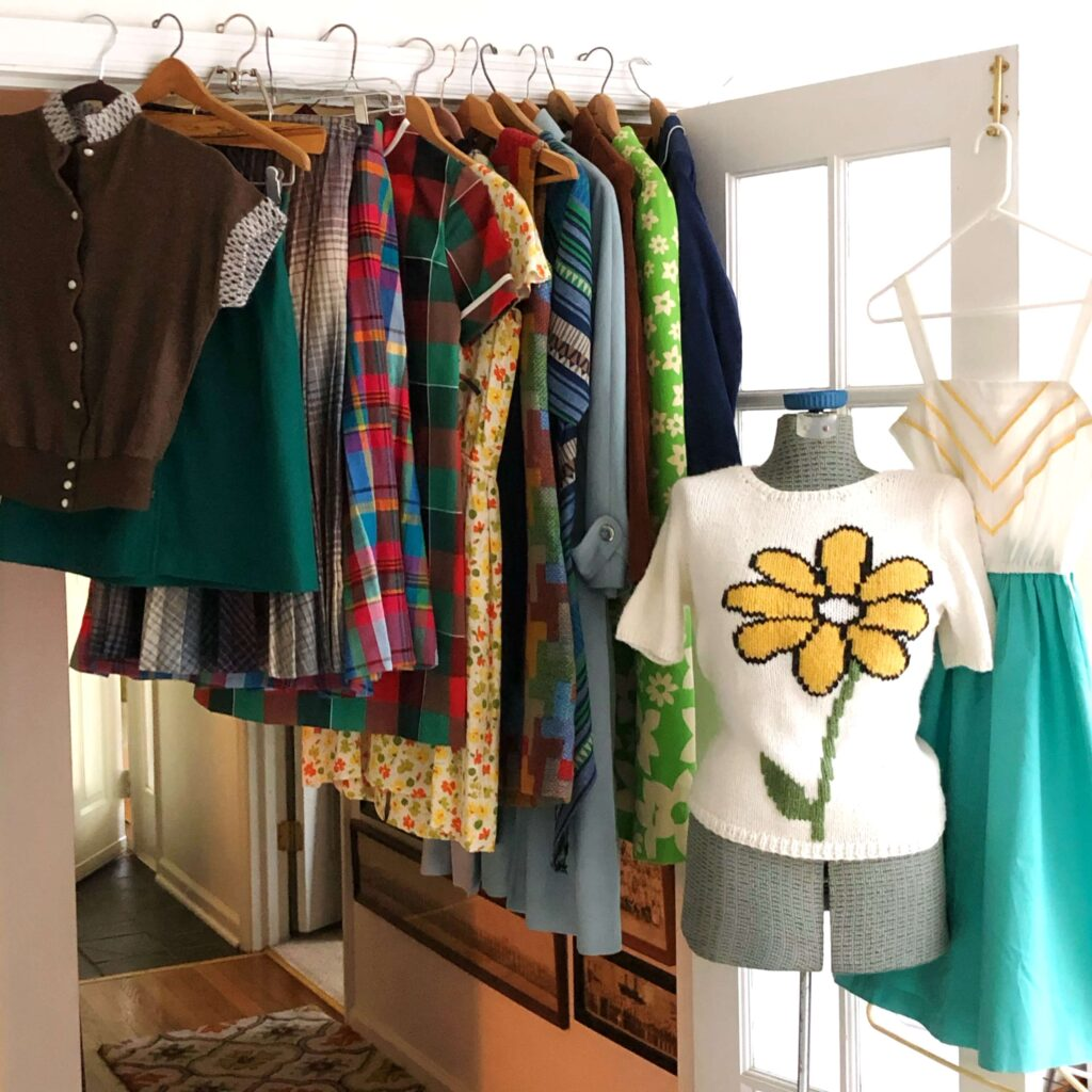 Vintage clothing hangs on a doorway, and a manikin displays a white sweater with a yellow flower.