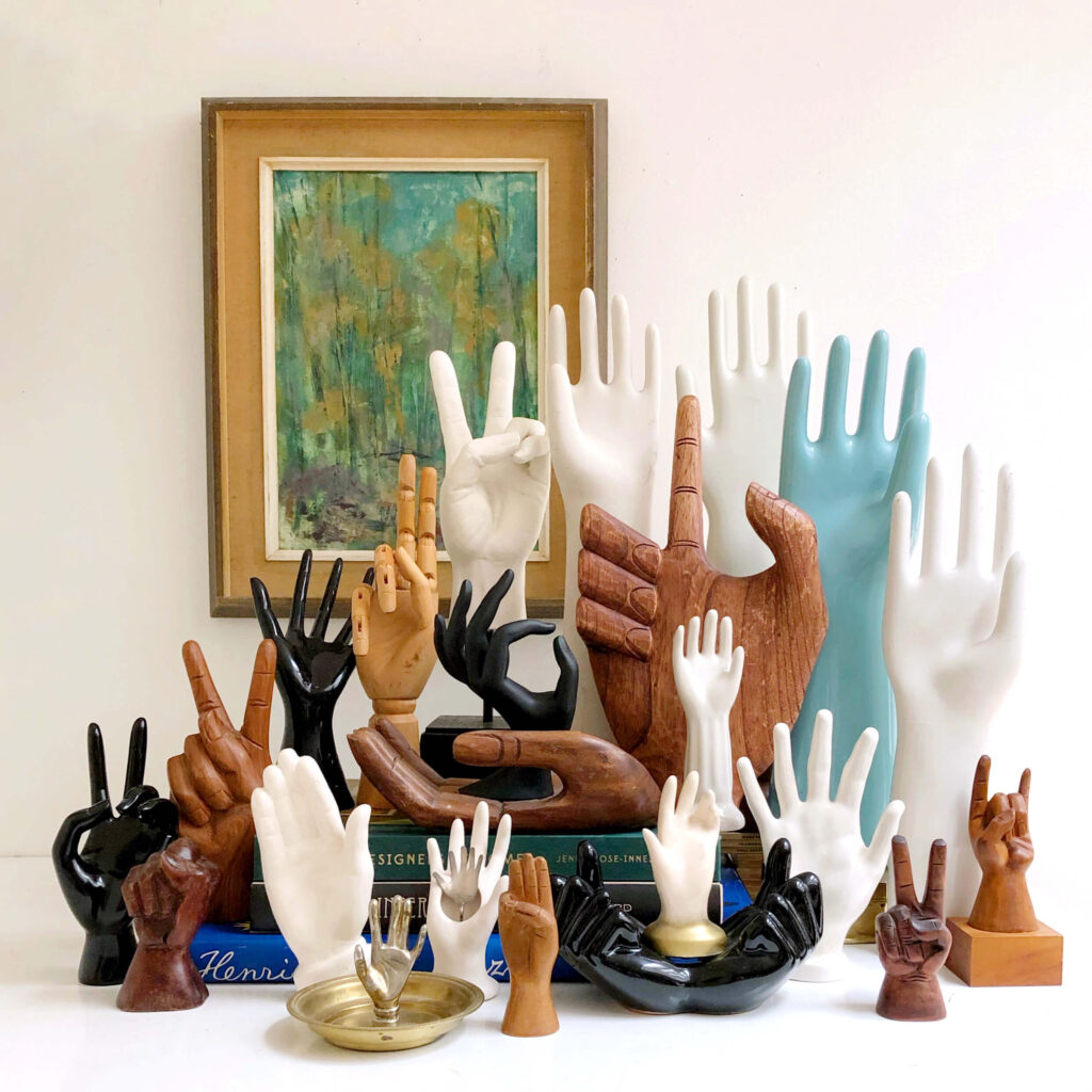 A collection of vintage hand sculptures made of wood, porcelain and plastic.