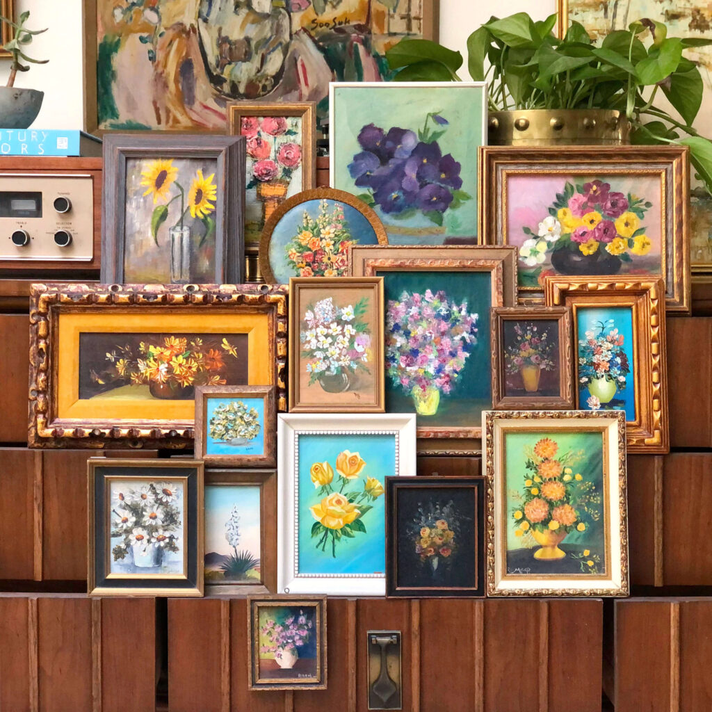 A collection of small vintage flower paintings are grouped together to form a makeshift gallery.