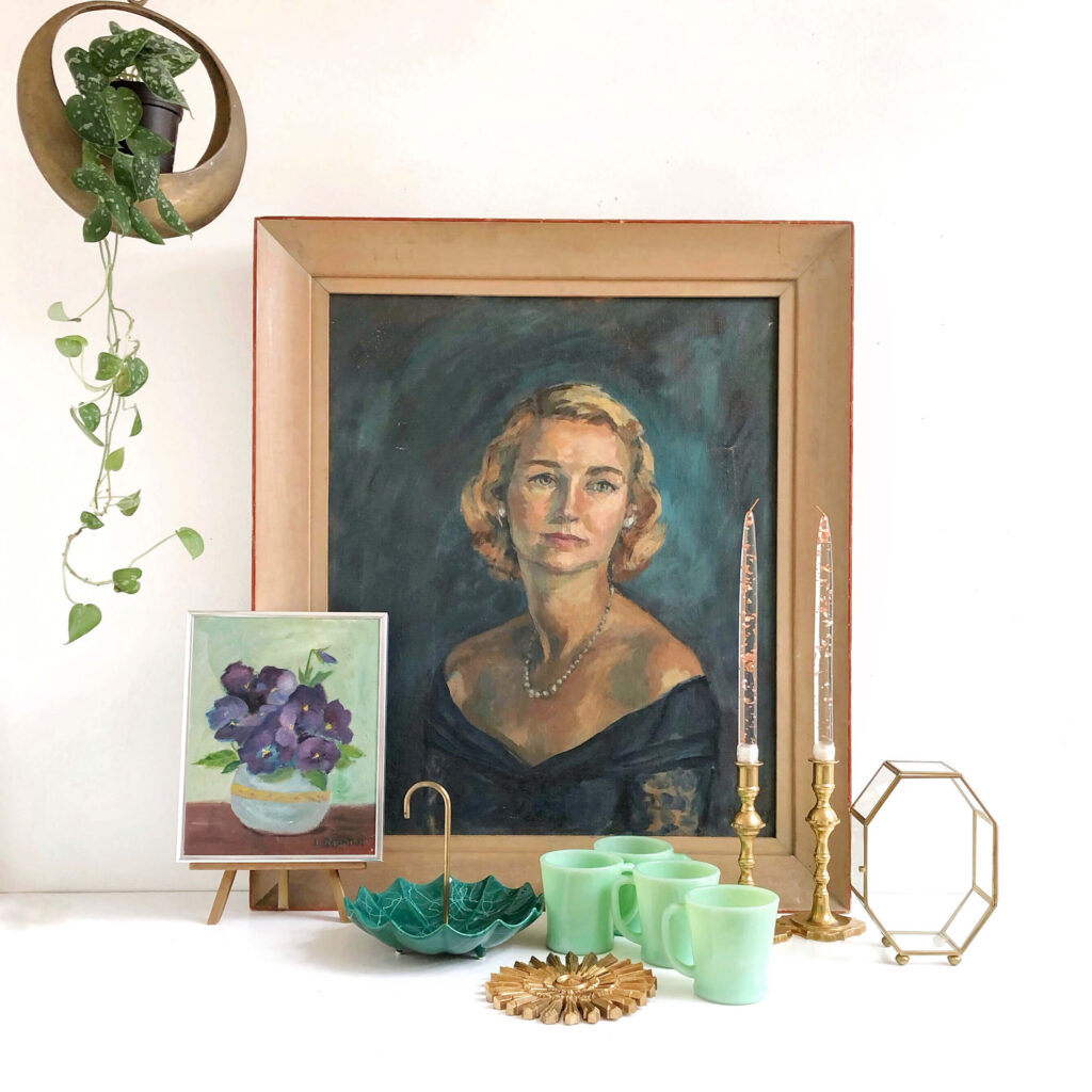 This vignette contains a portrait painting, jadeite cups, a mini flower painting and candlesticks.