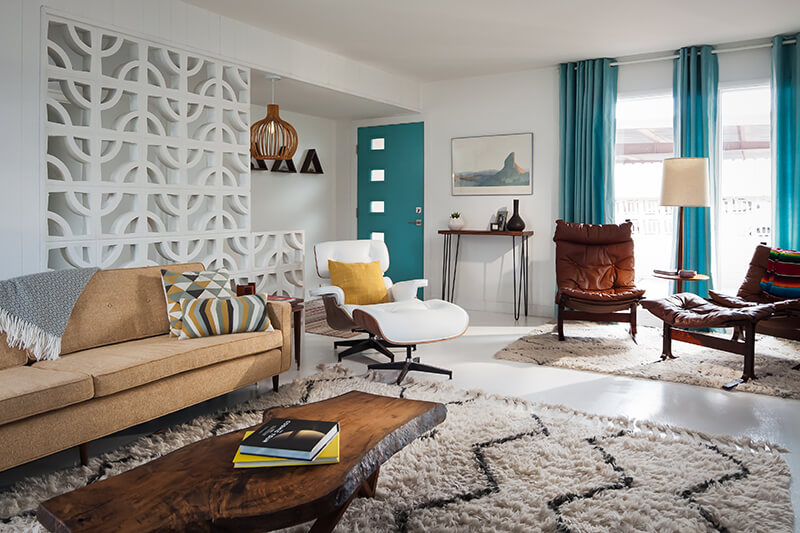 Mid Century living room with teal accents, a white Eames chair, shag carpet and a white breeze block entryway.