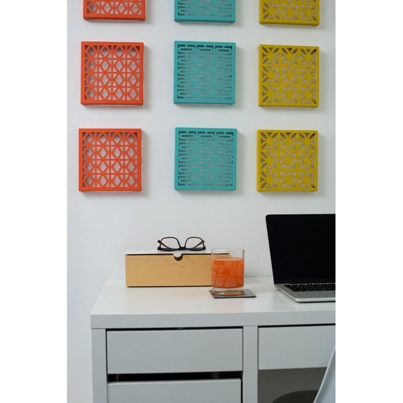 Colorful breeze block wall art in peach, teal and mustard yellow hang above a desk