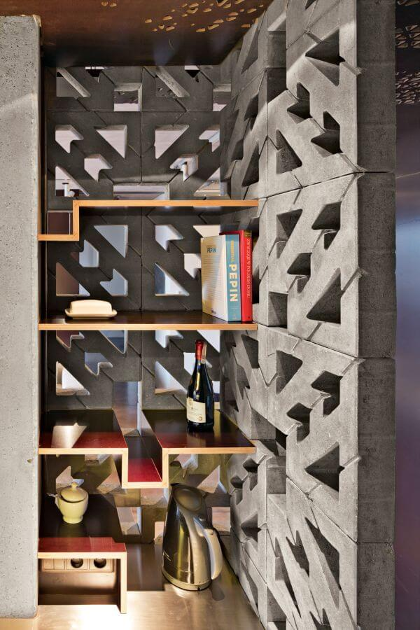 Gray concrete blocks with an arrow pattern form a shelving unit