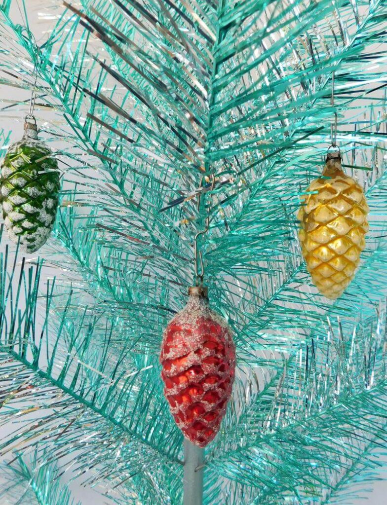 Teal aluminum Christmas tree with colorful pinecone ornaments