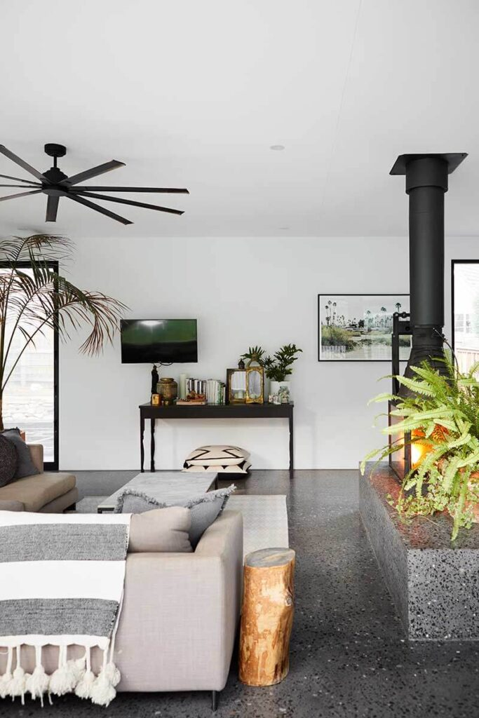 Open modern space with concrete floor, gray couch, a small tv and a table filled with collectibles