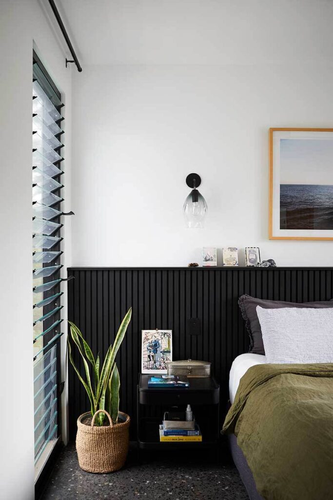 Contemporary bedroom with black wainscoting, olive green bed comforter and plant