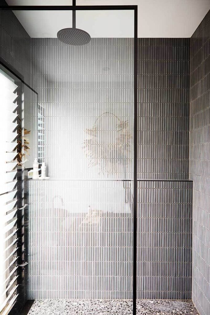 Contemporary gray bathroom with finger tiles in the shower