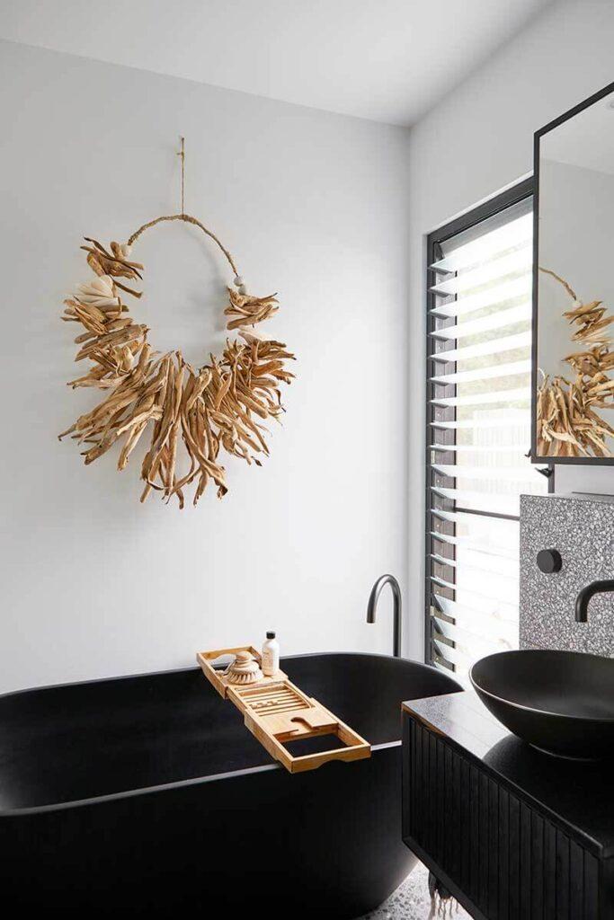 Black bathtub with wood art piece hanging above it
