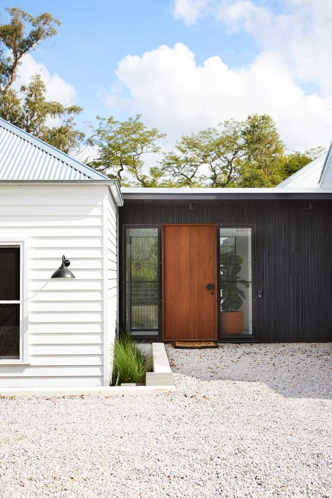 Back entrance to a home in NSW. Warm wood door with black feature wall.