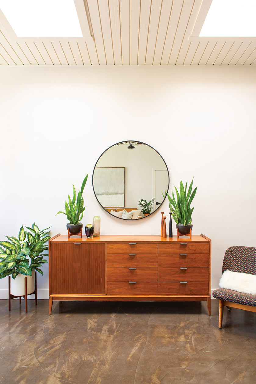 Mid century credenza with circle mirror and house plants