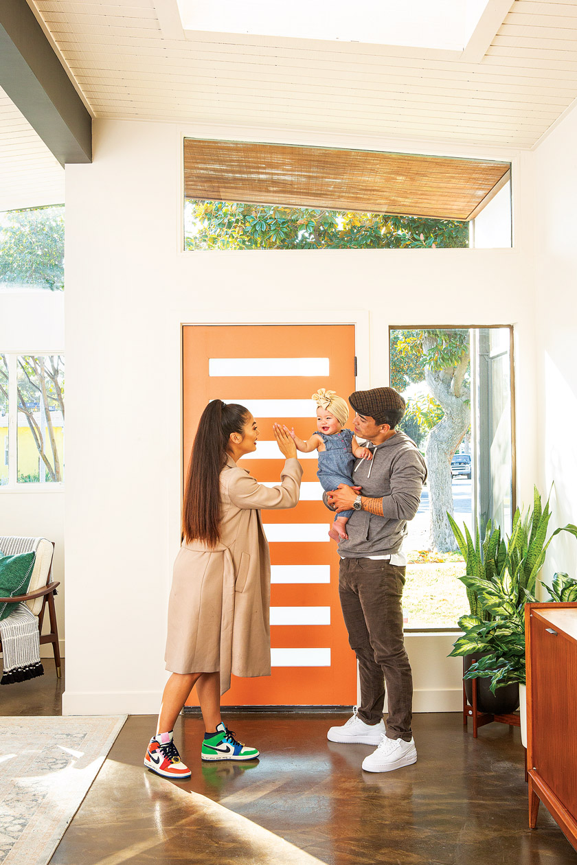 Homeowners Keven and Alana share a family moment near their orange door.