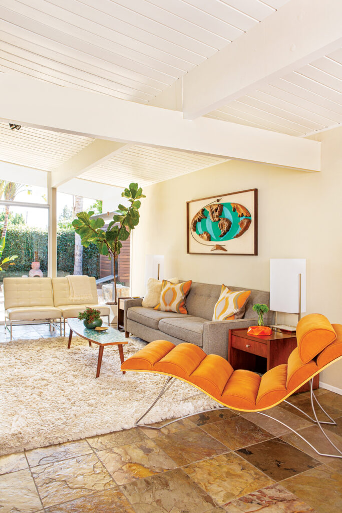 MCM-style licing space with an orange chair, shag rug and globe art