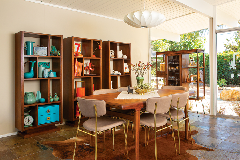 MCM dining room in a 1960s Eichler with three bookshelves filled with colorful decor