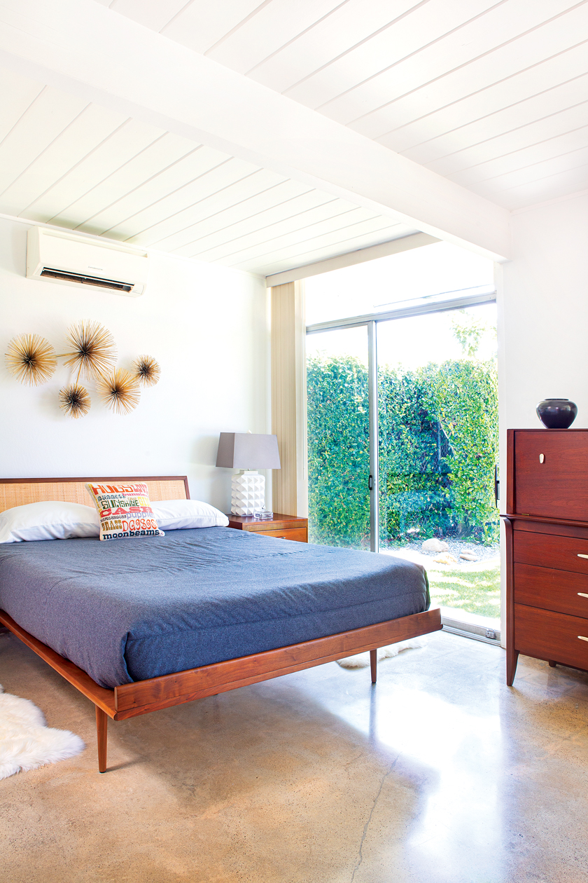 Master bedroom in an Eichler getaway with urchin art above the bed and views to the outdoors