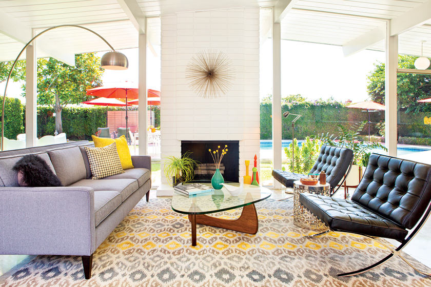 Mid Century Modern living room with an original white brick fireplace that looks out onto a backyard pool