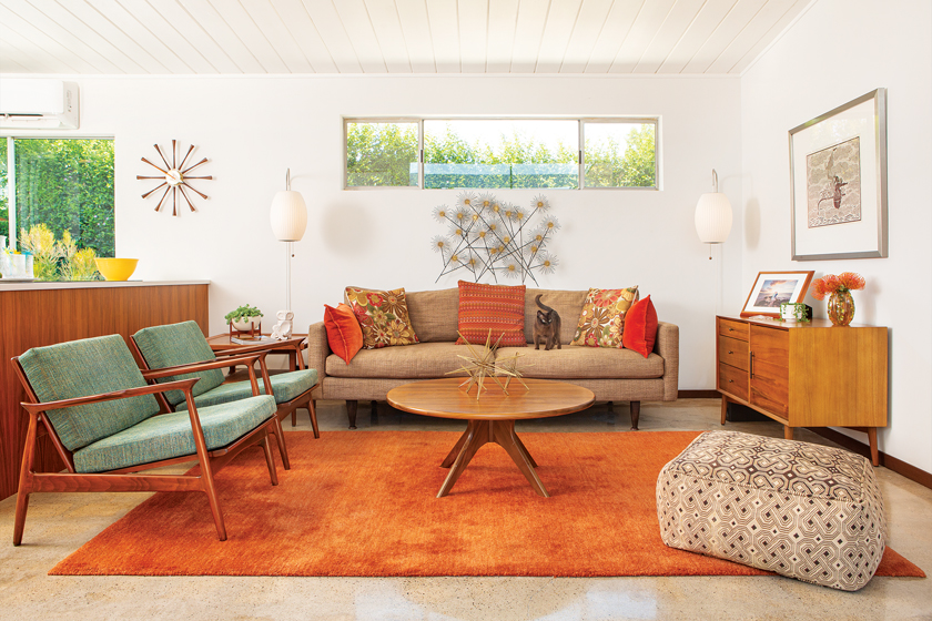 MCM living room with an orange rug, modern wall art and other mid century-style furniture.
