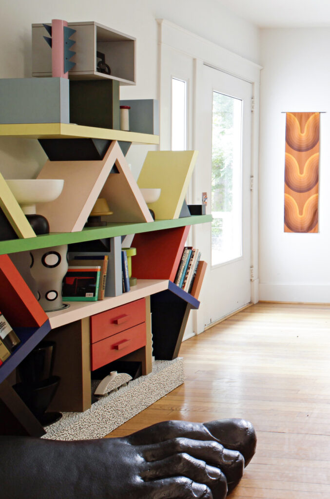 Colorful shelving unit in pink, yellow, red, blue and black with a modern tapestry on wall.