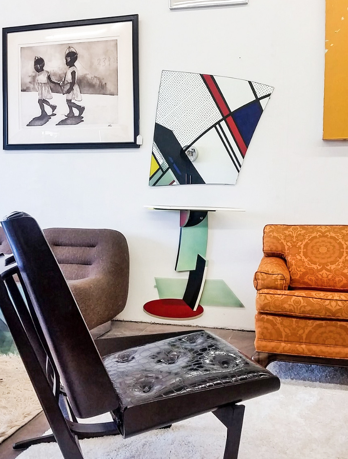 A post modern console table in mostly primary colors flanked with a mid century orange sofa and brown space age chair. A Roy Lichtenstein style mirror on wall.