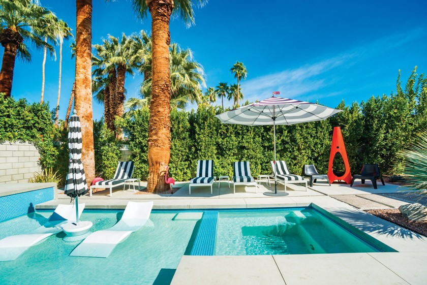 Desert Eichler pool with original Palm Trees and striped lounge chairs