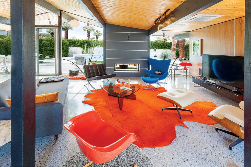 MCM Living room with orange rug, gray fireplace and terrazzo floors