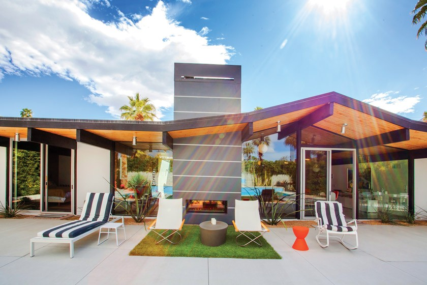Desert Eichler backyard exterior showcasing the roof shape and the exterior of the gray fireplace