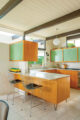 Mid century modern kitchen with mint green peg board cabinet doors
