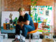 Andrew Cooper, Male, mid 20's artist sitting on chair in painting studio with canvases and art.