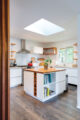Open kitchen with white island and embedded wine rack, open shelves and skylight